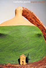 <h5>Donna Val d'Orcia Verde</h5><p>Scultura di cartapesta omaggio alla Val d'Orcia con casina e cipressino di argilla.</p>