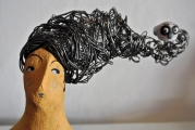 <h5>Volto di donna di Carlotta Parisi - Particolare</h5><p>Scultura in cartapesta. Dettaglio della capigliatura in fil di ferro con fischietto in argilla.</p>
