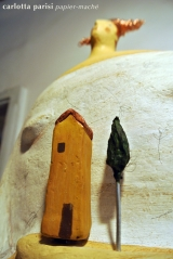 <h5>Donna Val d'Orcia di Carlotta Parisi  - Montalcino</h5><p>Casetta e cipresso in argilla su scultura di cartapesta.</p>